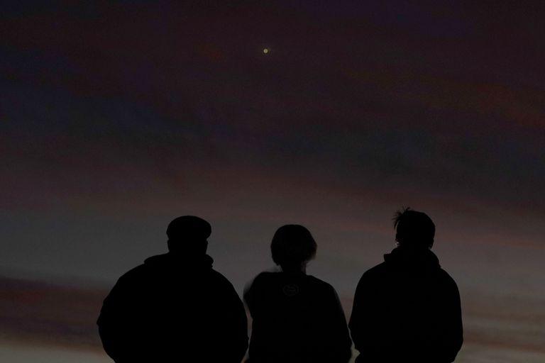 Tres personas observan el alineamiento de Júpiter y Saturno con la Tierra el pasado lunes en Kansas.