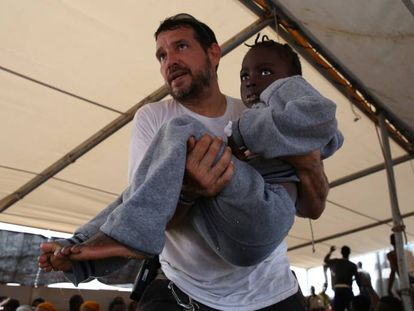 Inego, logista del Dignity I, lleva en brazos a una niña a la clínica de la nave.