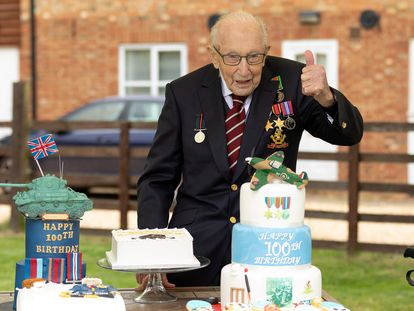 """A handout picture released on April 30, 2020 shows Captain Tom Moore posing for a photograph with cakes to celebrate his 100th birthday in Marston Moretaine, north of London. (Photo by Emma SOHL / CAPTURE THE LIGHT / AFP) / RESTRICTED TO EDITORIAL USE - MANDATORY CREDIT """"AFP PHOTO / CAPTURE THE LIGHT / EMMA SOHL"""" - NO MARKETING NO ADVERTISING CAMPAIGNS - DISTRIBUTED AS A SERVICE TO CLIENTS --- NO ARCHIVE ---"""