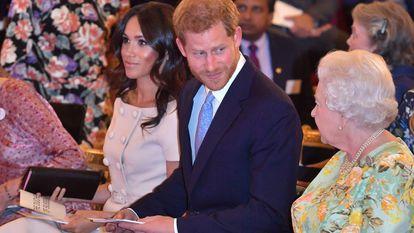 Isabel II, Enrique de Inglaterra y Meghan Markle, en una entrega de premios en el palacio de Buckingham en junio de 2018.