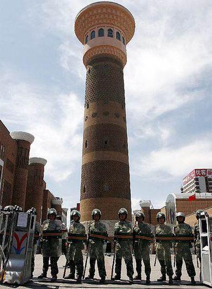Soldados pertrechados con material antidisturbios controlan el acceso a la mezquita de Urumqi.