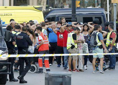 Un grupo de gente con los brazos en alto ante el despliegue policial en las Ramblas de Barcelona.