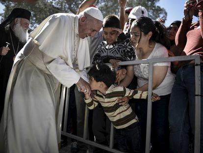 Un muchacho besa la mano al papa Francisco en el campo de refugiados de Moira, en la isla griega de Lesbos.