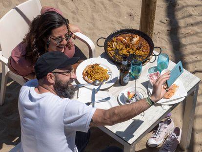 Dos comensales en la playa del Somorrostro en Barcelona. Carles Ribas