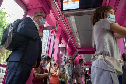 Pasajeros en un autobús en Ginebra (Suiza) se protegen con mascarillas.