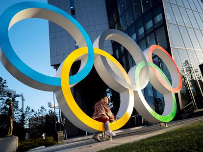 A child poses for photographs with the Olympic rings in front of the Japan Olympic Museum in Tokyo , Japan, February 17, 2020. REUTERS/Athit Perawongmetha