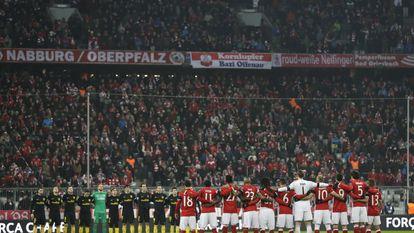 Los jugadores del Atlético de Madrid y del FC Bayern Munich, durante el minuto de silencio, antes del partido, en memoria de los miembros del equipo de fútbol brasileño Chapecoense.