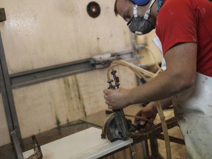 Un marmolista trabaja cortando cuarzo.