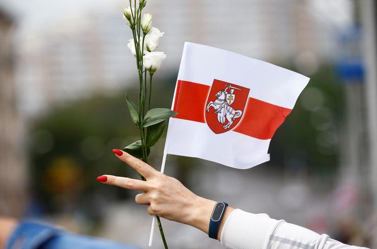 Una manifestante con flores, en la marcha de este sábado en las calles de Minsk contra el presidente Lukashenko.