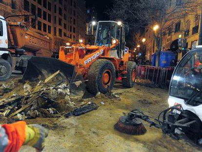 Los equipos de limpieza municipales retiran la pasada noche los restos de la 'cremà'.