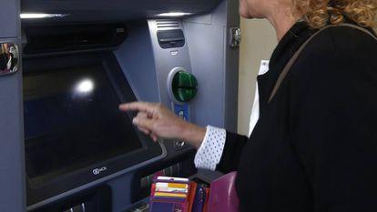 Una persona saca dinero de un cajero del Banco Sabadell.