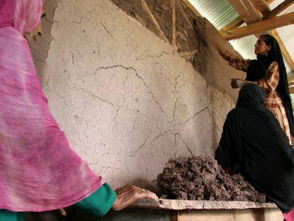 Unas mujeres reparan su casa en Pakistán.
