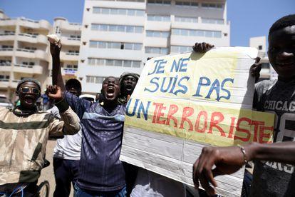 Varios manifestantes protestan por la detención del líder de la oposición Ousmane Sonko y sostienen una pancarta que dice 'No soy un terrorista' en Dakar, Senegal, el 8 de marzo de 2021.