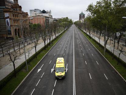 Una ambulancia circula por el paseo de la Castellana de Madrid, vacío durante el confinamiento, en abril de 2020.