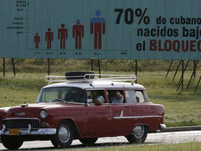 Un antiguo coche de fabricación estadounidense pasa ante un cartel sobre el bloqueo a la isla en La Habana.