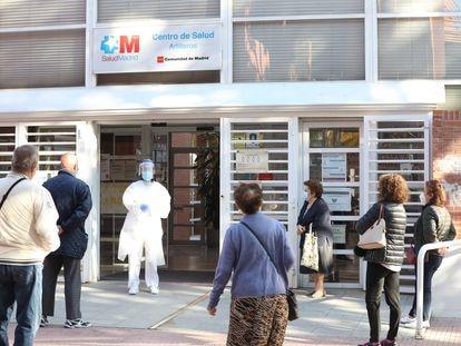 Una sanitaria sale a atender a numerosas personas que esperan fuera del Centro de Salud Artilleros, este martes.