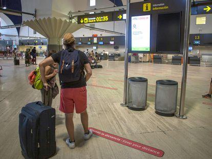 Pasajeros miran las pantallas informativas en la terminal de salidas del aeropuerto de San Pablo, Sevilla, el 19 de agosto.