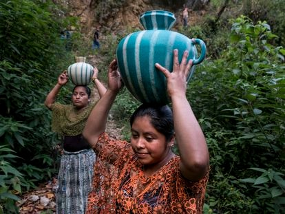 Mujeres guatemaltecas transportando agua desde el río en Chiquisis, San Pedro Carcha (Guatemala).