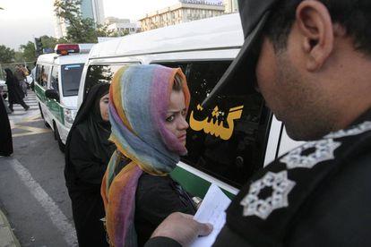 Un agente toma el nombre de una mujer detenida en Teherán.