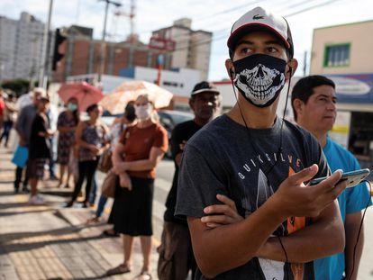 Un hombre espera para recibir un subsidio del Gobierno por la pandemia en São Paulo, Brasil.