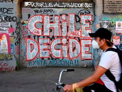 Un hombre en bicicleta pasa este viernes 23 de octubre delante de una pintada callejera que llama a votar en el plebiscito constitucional del domingo.