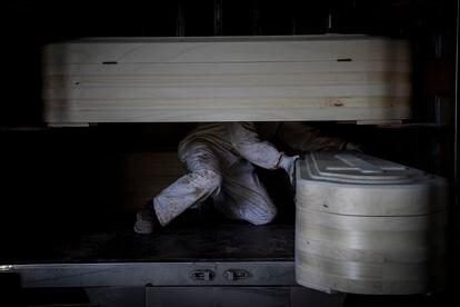 Un trabajador de una fábrica de féretros de Piñor (Ourense) prepara cajas destinadas a la incineración de cadáveres durante la crisis sanitaria.