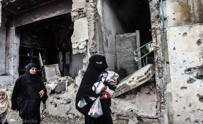 Un par de mujeres caminan con sus hijos frente a un edificio en ruinas de la ciudad siria de Raqa.