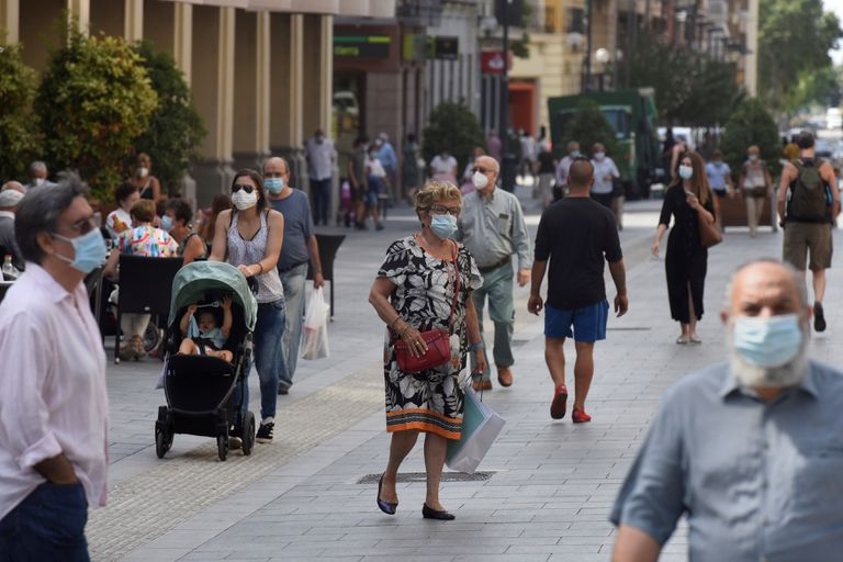 Varias personas con mascarilla caminan por las calles de Huesca este martes.