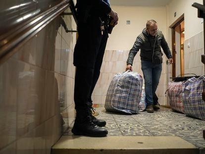Rachid El Yagoubi saca, en presencia del un policía, sus pertenencias del piso del que ha sido desahuciado este viernes