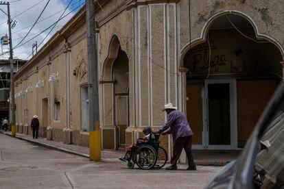Un hombre empuja una silla de ruedas frente a un hotel quemado por el narcotráfico en la plaza principal de Aguililla.