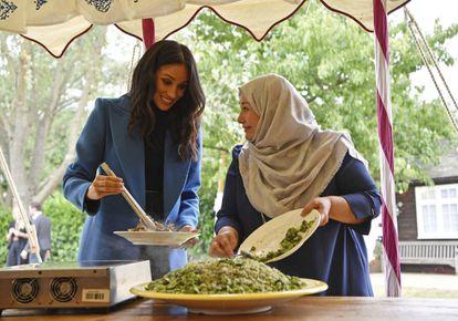 Meghan Markle junto a una mujer que forma parte del proyecto de cocina comunitaria.