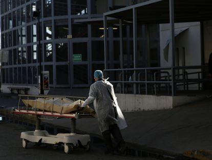 Un trabajador sanitario mueve el cuerpo de un fallecido por covid-19 en Ciudad Juárez.