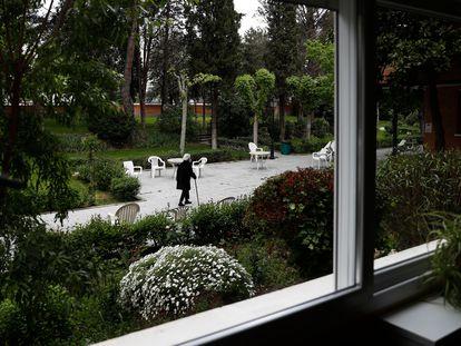 Una anciana pasea por el jardín de una residencia de Madrid.