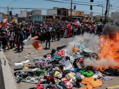 Grupo de personas queman carpas que eran utilizadas por extranjeros para pernoctar en plazas y playas, durante una marcha contra la migración irregular el sábado, en Iquique (Chile).