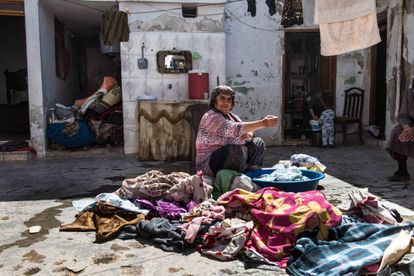 Las desplazadas de Afrin lavan a mano cortinas, sábanas y toallas antes de asentarse en aquellas casas del poblado de Tel Rifat previamente abandonadas por sus dueños durante los combates.
