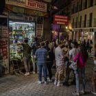 Varias personas hacen cola en una tienda de alimentación del centro de Madrid pasadas las 23:00 horas.