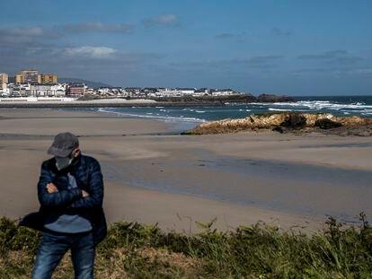 Un vecino de Barreiros pasea por el entorno del arenal de la playa de Altar, con la vecina localidad de Foz al fondo.