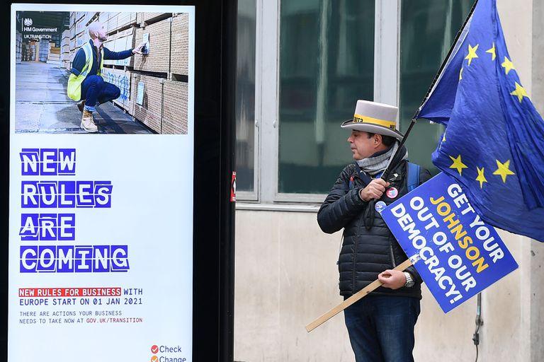 El activista Steve Bray sostiene una bandera de la UE frente una parada de autobús con un anuncio proBrexit en Westminster, en Londres, el miércoles.