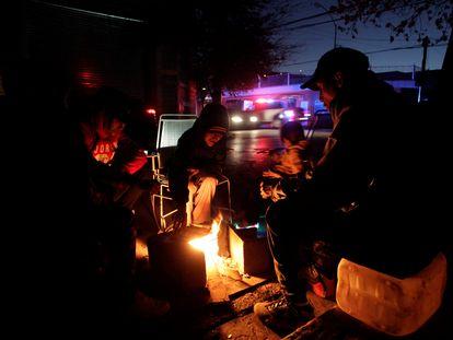 Una familia calienta tortillas en una pequeña hoguera a las afueras de su casa en Monterrey, afectada por el apagón masivo.
