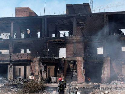 Un bombero trabaja en las labores de extinción del incendio con varias explosiones, originado en un edificio okupado del barrio de Es Viver de Ibiza.