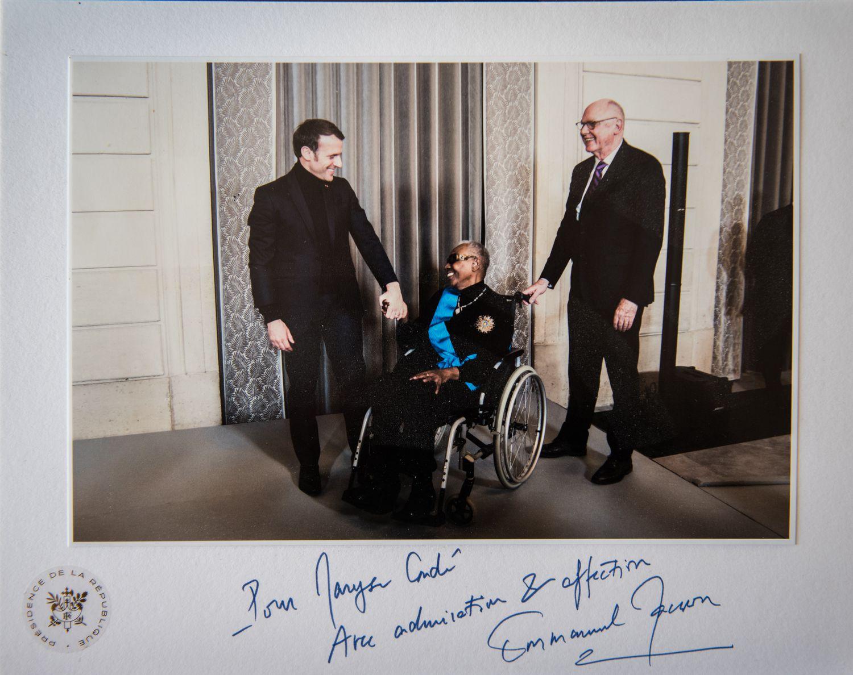 """Maryse Condé junto a su marido y el presidente Emmanuel Macron en una fotografía de la presidencia de la Républica. Ceremonia de condecoración de la """"Gran cruz de la orden del mérito nacional""""."""