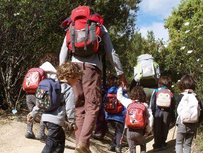 Varios niños con sus acompañantes suben a la pradera de Collado Mediano donde aprenden con su Grupo de Juego en la Naturaleza Saltamontes.