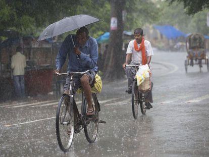 Varios hombres indios andan en bicicleta bajo la lluvia en Allahabad, en plena temporada del monzón en la India.