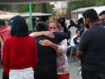 Familiares de víctimas del accidente en el metro de Ciudad de México se abrazan a las puertas de la oficina forense de Iztapalapa.