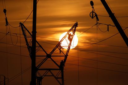 Technicians work on a power tower while maintaining high-voltage power lines.