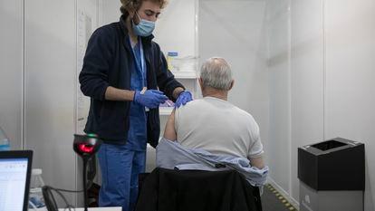 Un enfermero vacuna contra la covid a un hombre el pasado mayo en Barcelona.