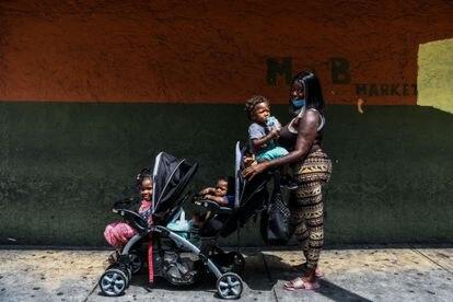Una mujer posa junto a sus tres hijos en un barrio afroamericano de Miami (EE UU).