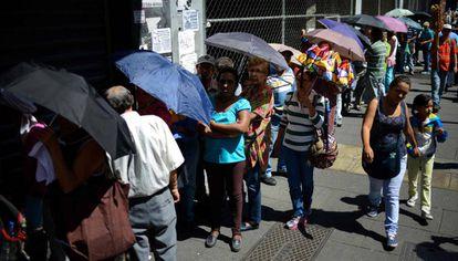 Un grupo de personas hace cola a las puertas de un supermercado en Caracas.