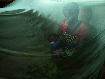Violet Wilson y su hijo de cinco meses descansan debajo de una mosquitera en su casa de Nkwazi, Malawi.