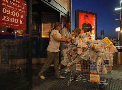 Unos clientes abandonan el hipermercado de Carrefour en Alcobendas pasadas las diez de la noche.